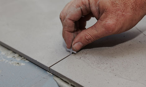 Placing the spacer between the flooring tiles